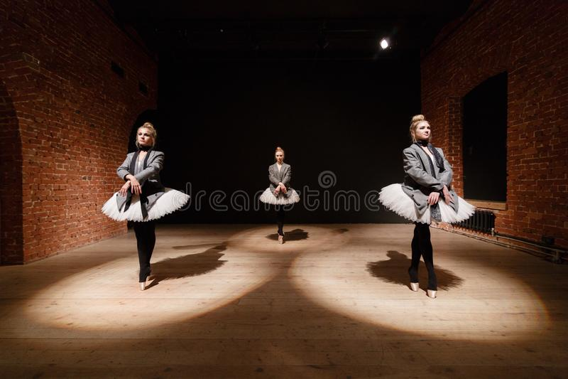 Het balletconcept Jonge ballerinameisjes Vrouwen bij de repetitie in een witte tutu en een grijs jasje Bereid a voor stock foto