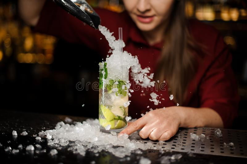 Het barmeisje voegt aan mojito verpletterd ijs toe stock foto's