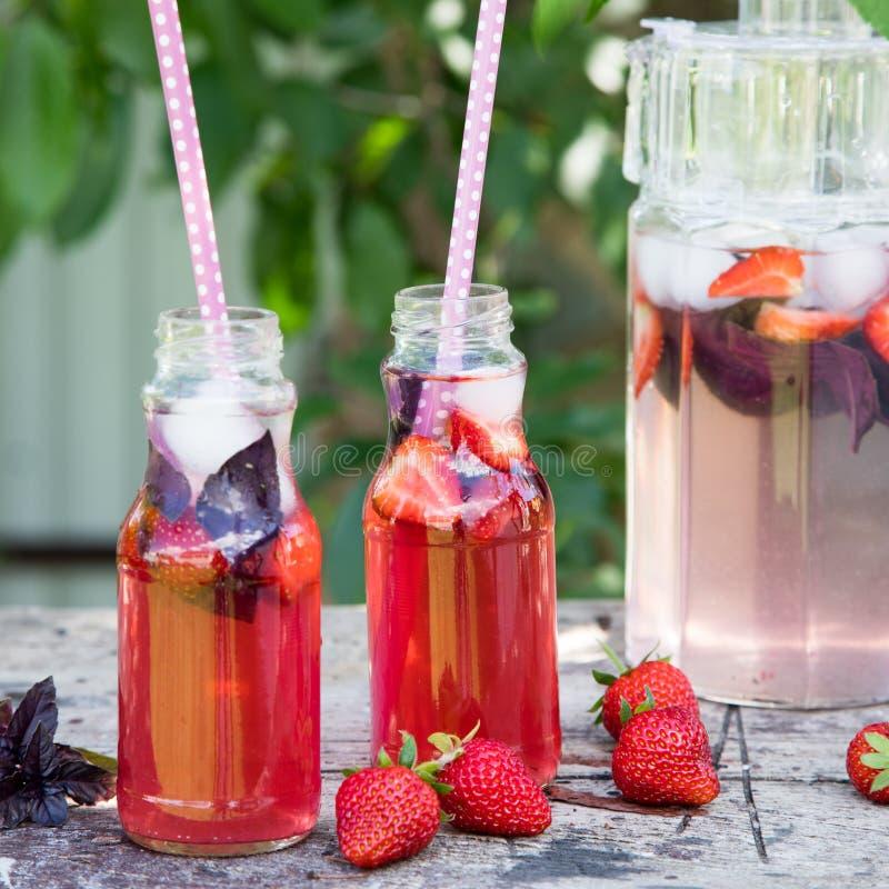 Het basilicum van de limonade detox aardbei verfrissende drank met verse streptokok stock afbeelding