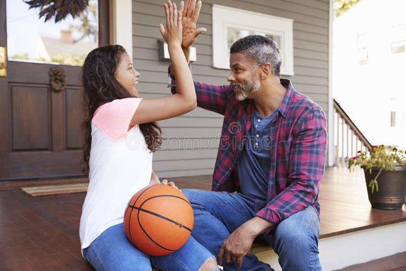 Het Basketbal van vaderand daughter discussing op Portiek van Huis royalty-vrije stock foto's