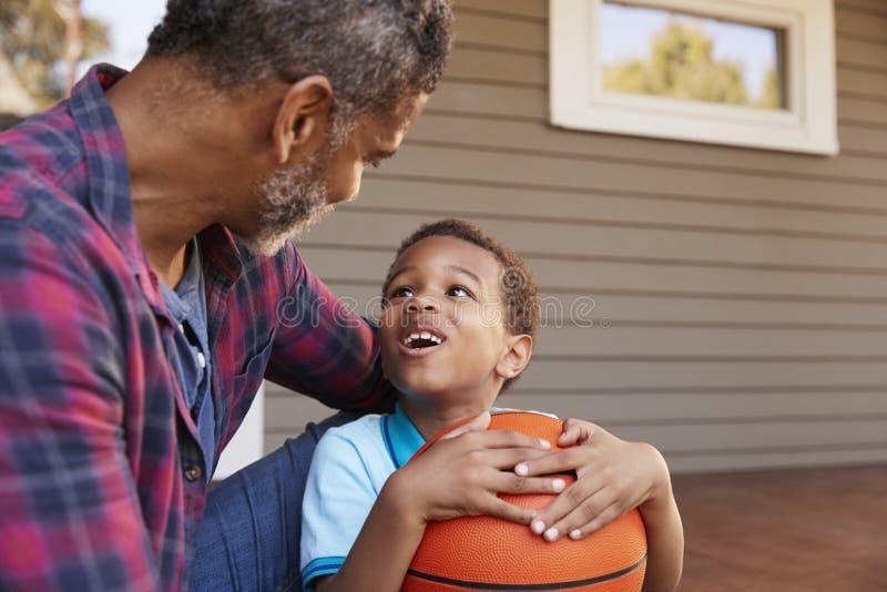 Het Basketbal van vaderand son discussing op Portiek van Huis royalty-vrije stock foto's
