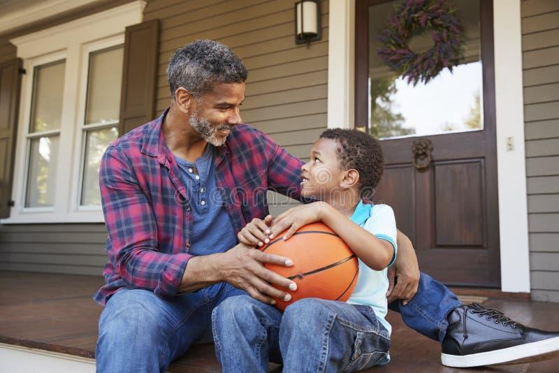 Het Basketbal van vaderand son discussing op Portiek van Huis royalty-vrije stock afbeeldingen