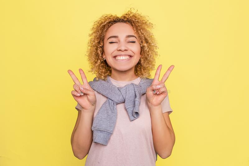 Het Beautifylmeisje glimlacht en toont een stuksymbool met vingers op haar handen Geïsoleerd op gele achtergrond stock foto
