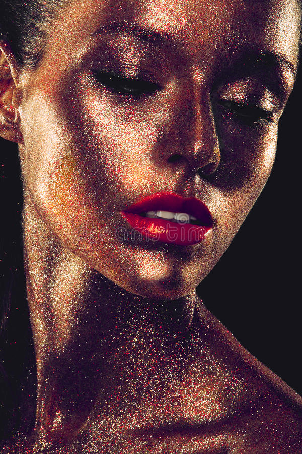 Het Beautyfulmeisje met goud schittert op haar gezicht stock afbeeldingen