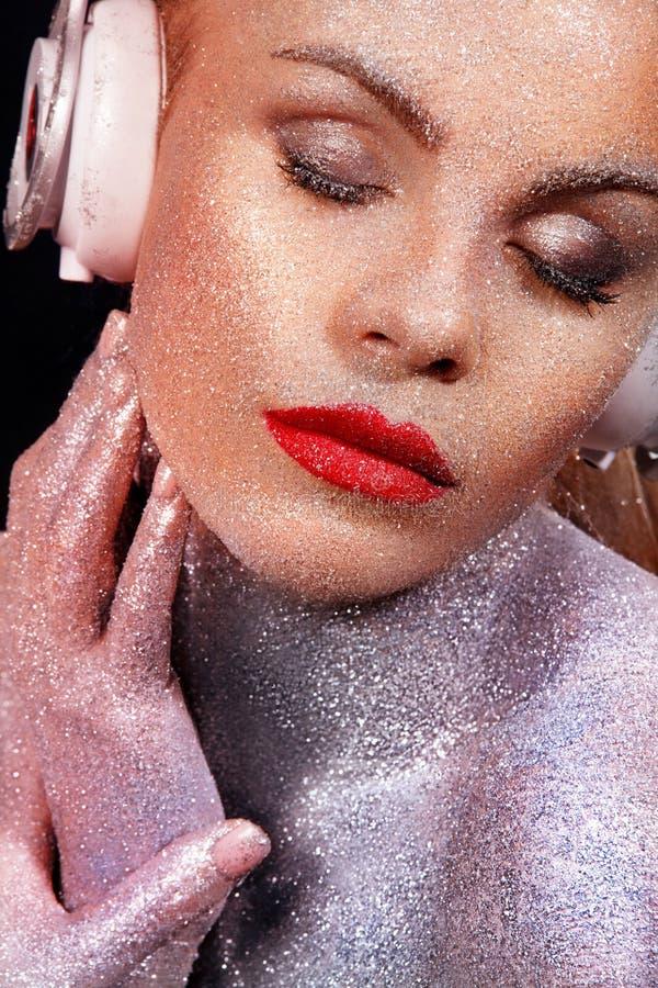 Het Beautyfulmeisje met schittert en fonkelingen op haar gezicht en lichaam Portret van sexy TDJ met hoofdtelefoons stock foto's