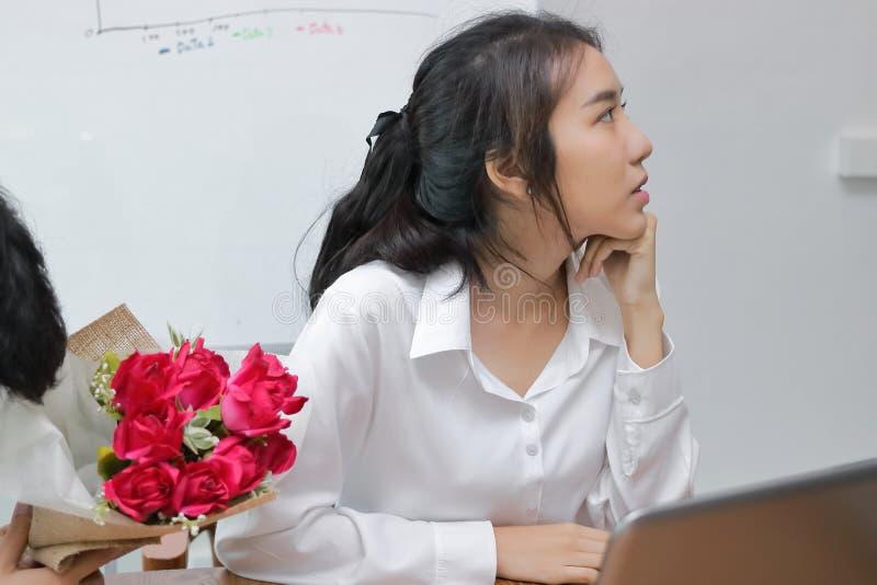 Het bebouwde beeld van boze Aziatische vrouw weigert een boeket van rode rozen van de bedrijfsmens Teleurgesteld liefdeconcept stock foto's
