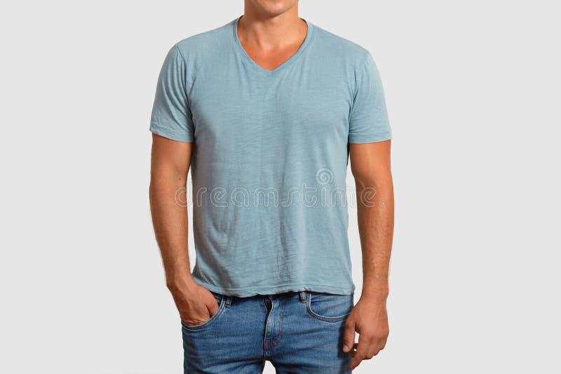 Het bebouwde beeld van de knappe mens draagt lege t-shirt, houdt indient zak, gekleed die in jeans, over witte achtergrond worden stock foto