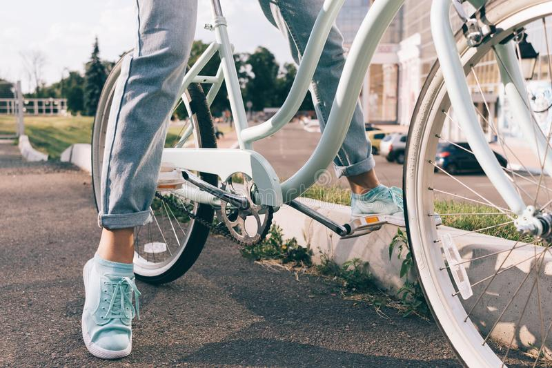 Het bebouwde beeld van een meisje in jeans en tennisschoenen zit op een fiets stock foto