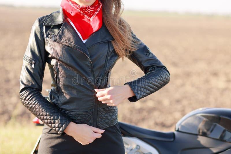 Het bebouwde beeld van het leer van vrouwenpitten het zwarte jasje, rode bandana op hals draagt, treft voor motorrbikeras voorber stock fotografie