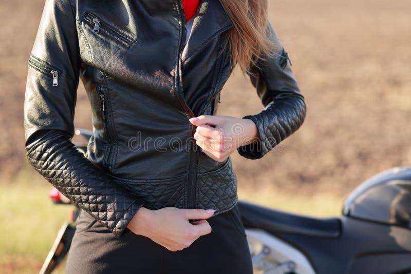 Het bebouwde beeld van modieuze vrouwelijke motorrijder snelt zwart leerjasje, heeft lichaamsbescherming, voorbereidingen treft v royalty-vrije stock afbeelding