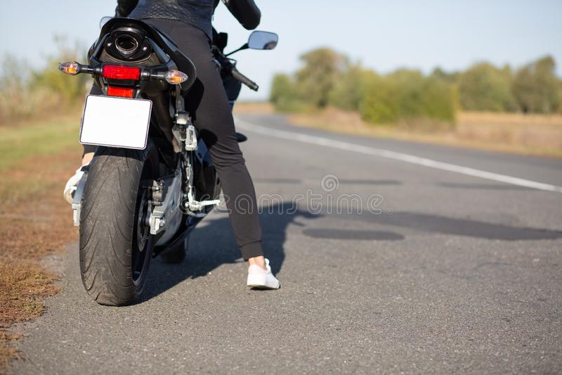Het bebouwde beeld van onherkenbare vrouwelijke fietsen stelt terug op fiets bij asfalt, draagt opzij zwarte kleren, lege exempla royalty-vrije stock foto's