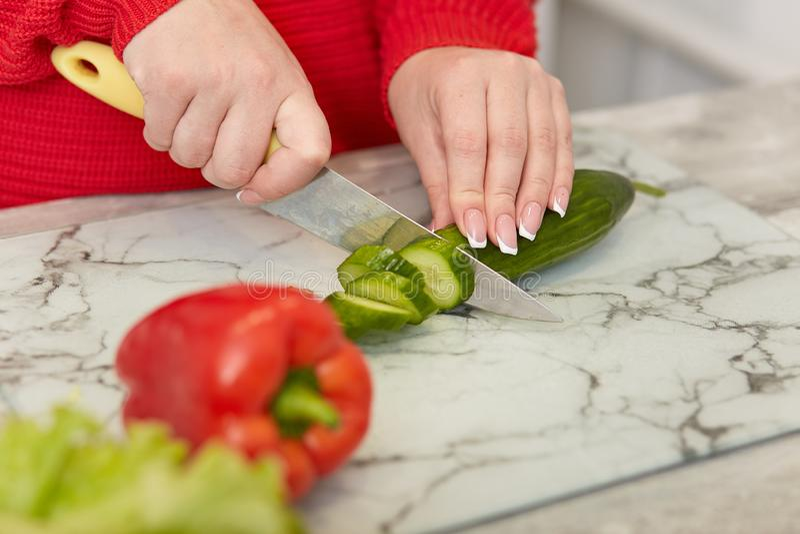 Het bebouwde beeld van vrouw met manicure snijdt verse komkommer, peper, maakt vegetarische salade thuis, gekleed in rode kleren, stock afbeelding
