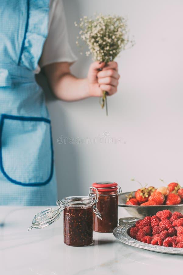 het bebouwde beeld van vrouw in schortholding bloeit dichtbij lijst met frambozen, aardbeien en kruiken royalty-vrije stock afbeeldingen