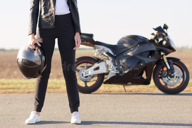 Het bebouwde horizontale schot van vrouwelijke fietser gekleed in zwart leerjasje, broeken en witte tennisschoenen, houdt helm, b stock afbeelding