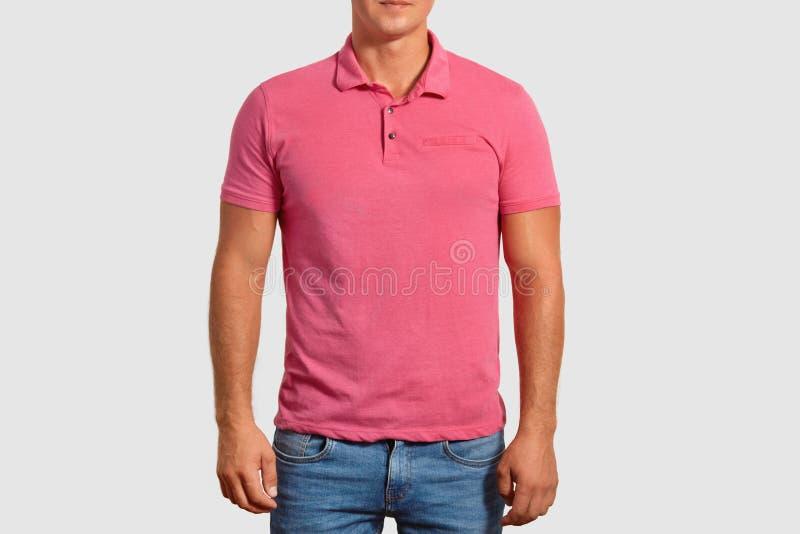 Het bebouwde schot van de jonge spiermens draagt toevallige roze t-shirt met lege ruimte voor uw reclame, jeans, stelt tegen wit stock foto