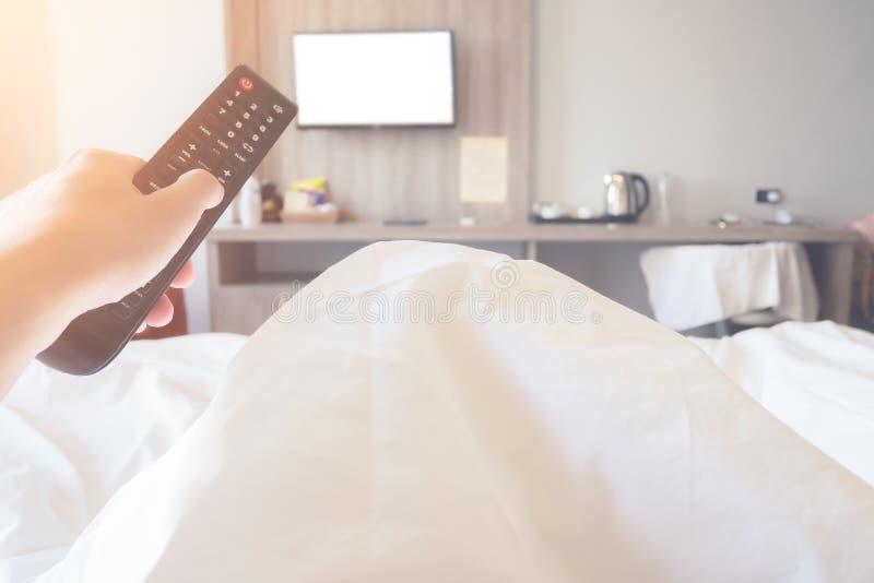 Het bed van de de afstandsbedieningtelevisie van de handholding ob in slaapkamer dichte omhooggaand stock afbeeldingen