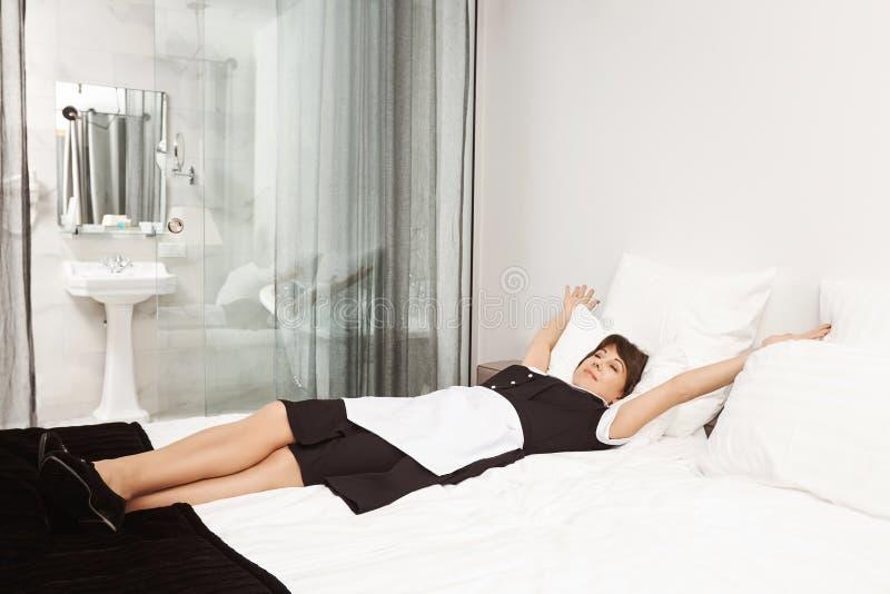 Het bed van de koningsgrootte voor koningin Ontspannen en onbezorgd dienstmeisje die en zich op bed, verlicht voelen liggen uitre stock afbeelding