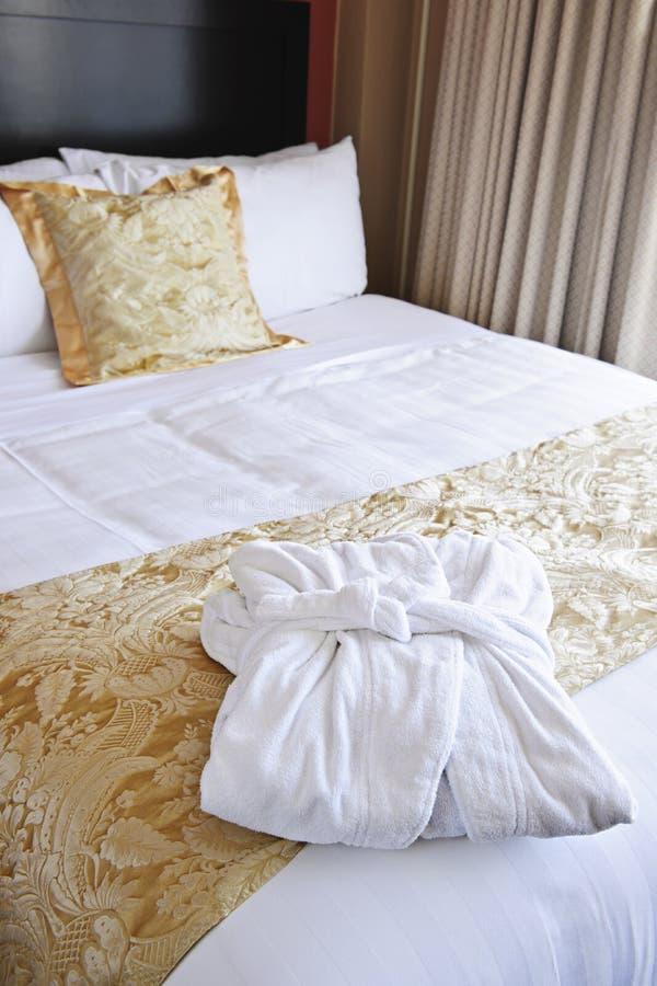 Het bed van het hotel met badjas royalty-vrije stock afbeeldingen