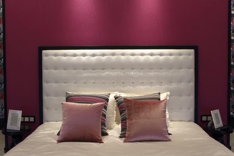 Het bed van wit, roze behang in de zolderslaapkamer met een meisje stock foto's