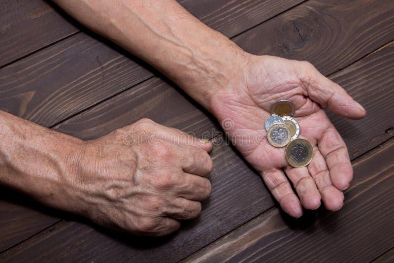 Het bedelen voor geld Bejaarde persoonshanden van bedelaar met weinig muntstukken Het concept armoede stock foto