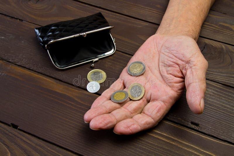 Het bedelen voor geld Bejaarde persoonshanden van bedelaar met weinig muntstukken Het concept armoede royalty-vrije stock foto's