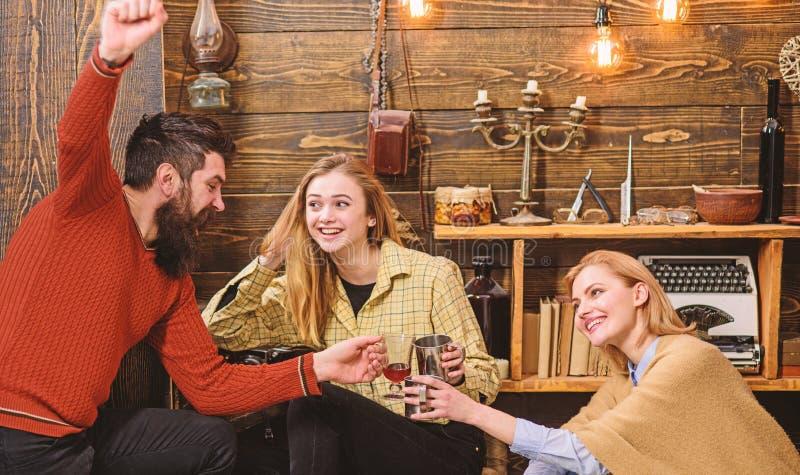 Het bedrijf van vrienden viert met overwogen wijn in comfortabele atmosfeer, houten achtergrond Juicht concept toe Mens en dames  stock foto