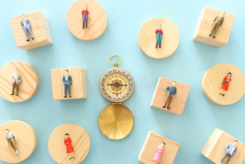Het bedrijfs conceptbeeld van groep miniatuurmensen en kompas Metafoor van de maatschappelijke structuur en sociale kwesties stock foto