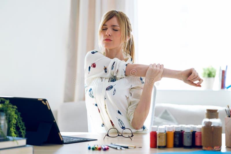 Het bedrijfs jong vrouw uitrekken zich lichaam voor het ontspannen terwijl het werken met digitale tablet in het bureau stock afbeelding