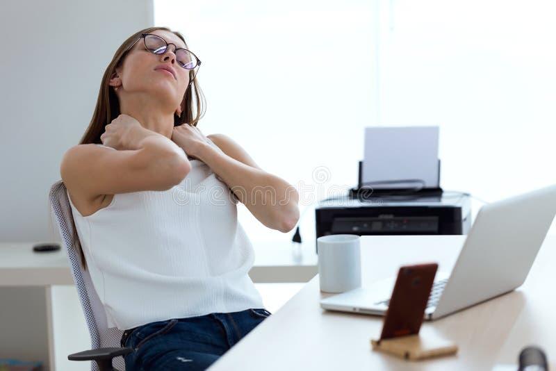 Het bedrijfs jonge vrouw ontspannen na het werken in het bureau royalty-vrije stock afbeeldingen