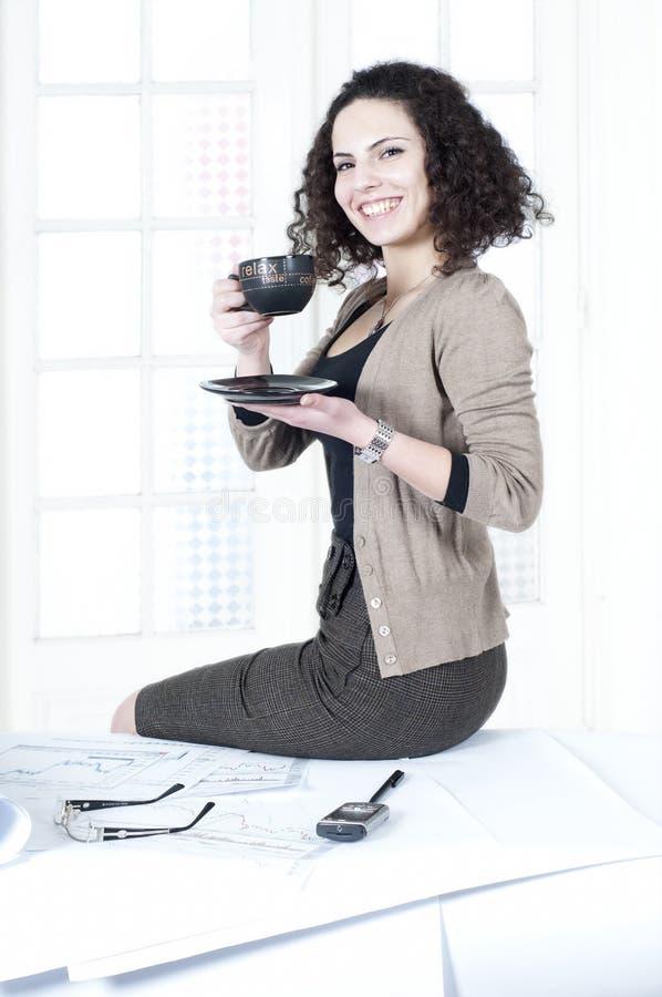 Het bedrijfs vrouw drinken koffie op het werk stock foto