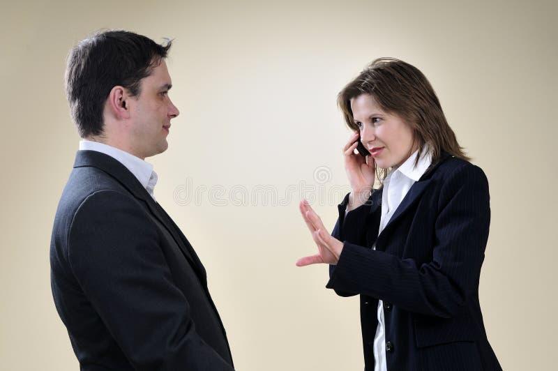 Het bedrijfs vrouw gesturing en man wachten stock afbeeldingen