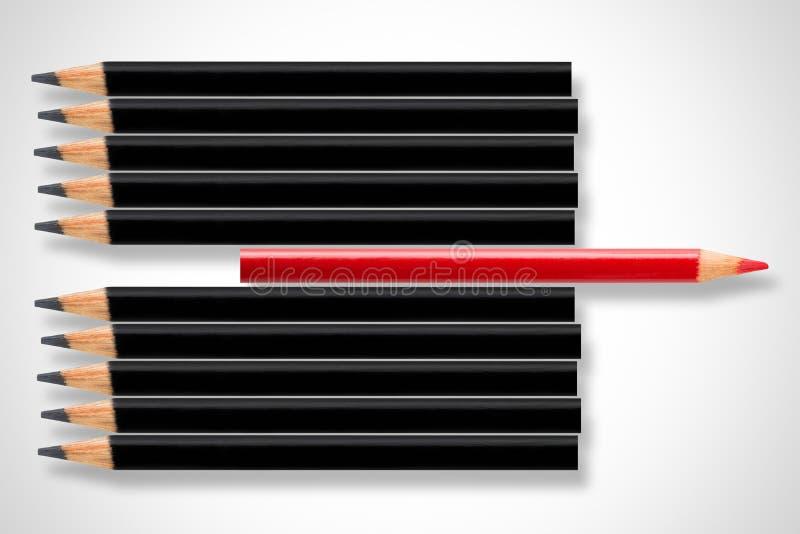 Het bedrijfsconcept verstoring, leiding of denkt verschillend; rood potlood in rij die van zwarte potloden in tegenovergestelde r stock fotografie