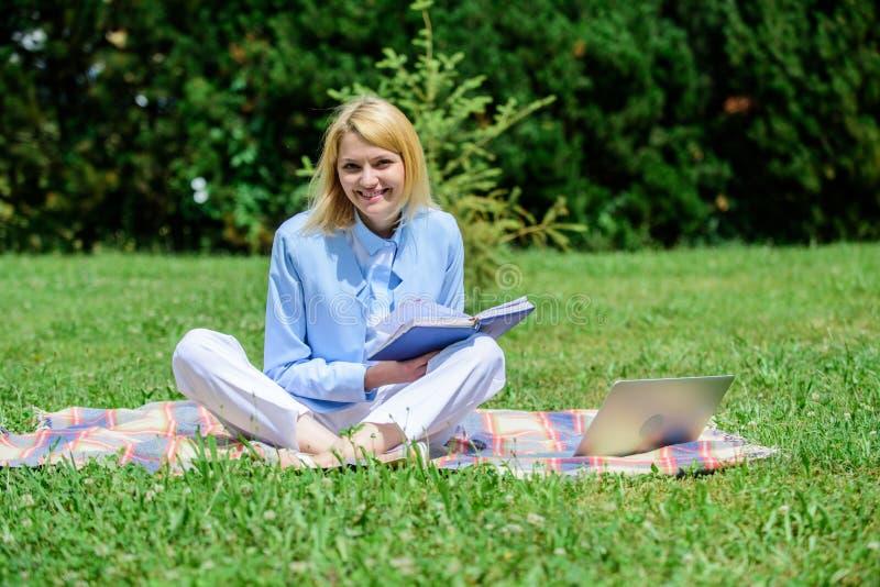 Het bedrijfsdame freelancer werk in openlucht Online bedrijfsidee?nconcept De vrouw met laptop of het notitieboekje zit op groene stock foto