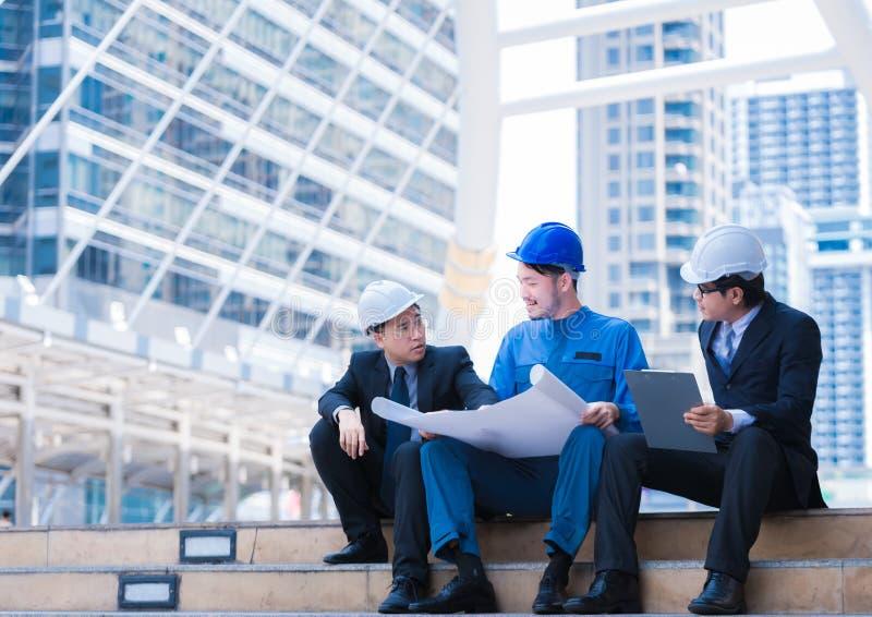 Het bedrijfsingenieur schaven met witte helm en het houden van tekeningsdocument tegen stads het achtergrond schaven en teambehee stock fotografie
