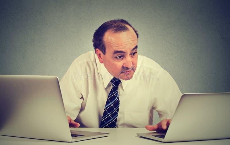 Het bedrijfsmens multitasking werken aan twee computers in zijn bureau stock afbeeldingen