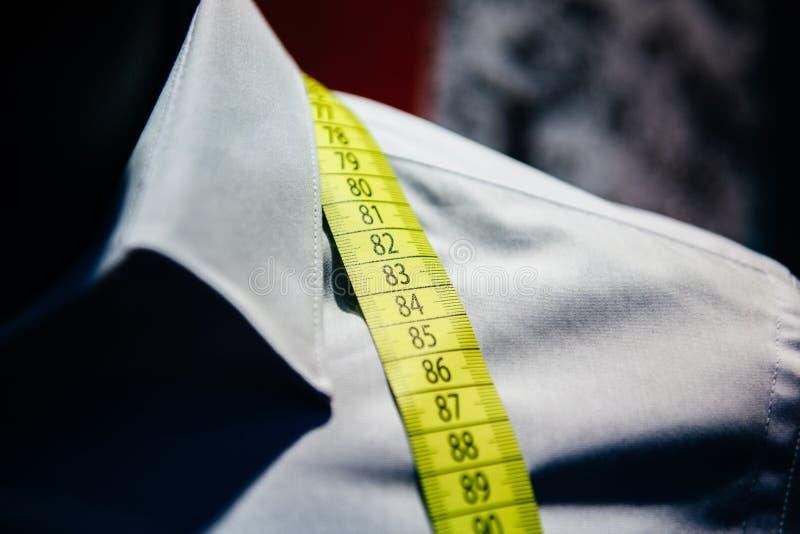 Het bedrijfsoverhemd maken op de band van de de ledenpopmaatregel van de kleermakerswinkel stock afbeeldingen