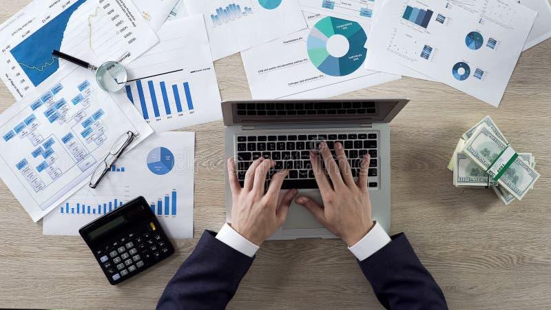 Het bedrijfspersoon typen op laptop, het verdienen stapels van dollars, hoogste mening, zaken stock afbeeldingen
