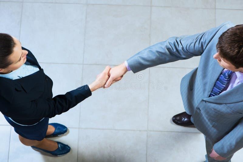Het bedrijfsvrouw en zakenman schudden handen stock afbeelding