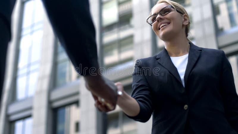 Het bedrijfsvrouw schudden hand met medewerker, tolk die van cliënt op de hoogte brengen stock afbeeldingen