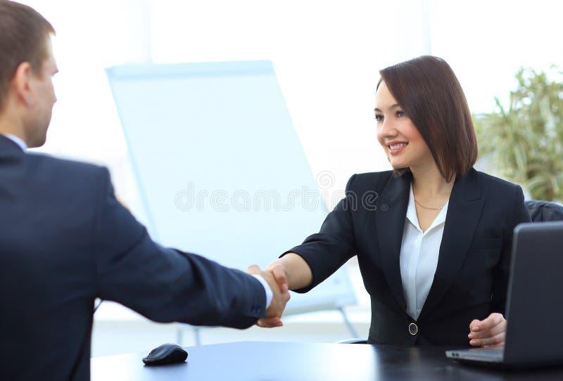 Het bedrijfsvrouw schudden handen met een partner over een Bureau royalty-vrije stock afbeeldingen