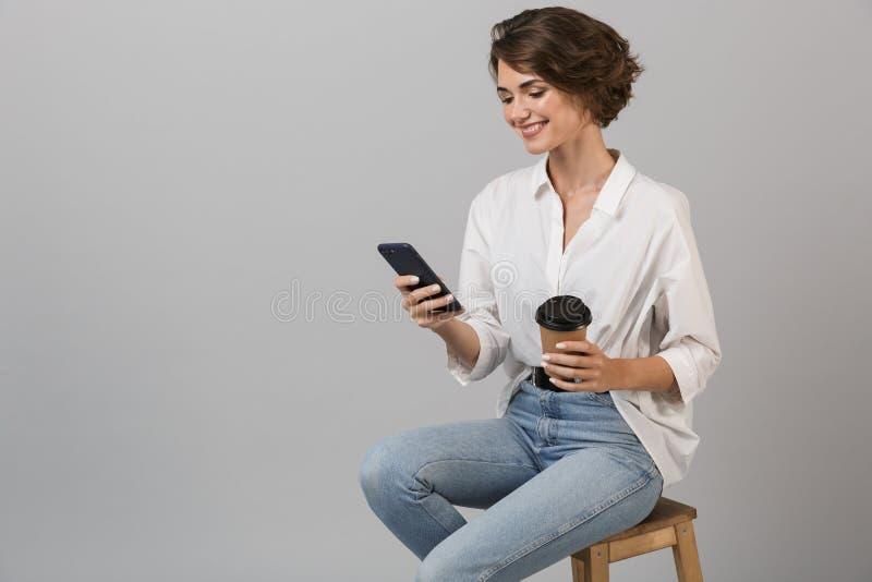 Het bedrijfsvrouw stellen geïsoleerd over grijze muurzitting als achtergrond op kruk die laptop computer met behulp van die telef stock foto's