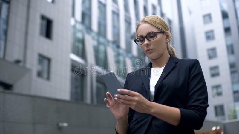 Het bedrijfsvrouw texting in smartphone, die tot lunch voor onderbreking opdracht geven online, app stock afbeeldingen