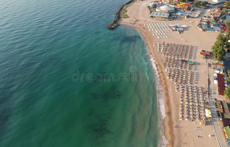 Het beeld uit de hoogte wordt genomen die een strand met veel paraplu's Het wachten op toeristen op de kust stock foto