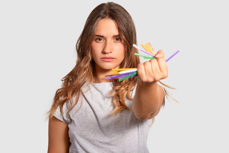 Het beeld van aantrekkelijk ernstig wijfje houdt verfrommelt plastic in hand stro, demonstraes haar sterk gevoel van het leven op stock foto's