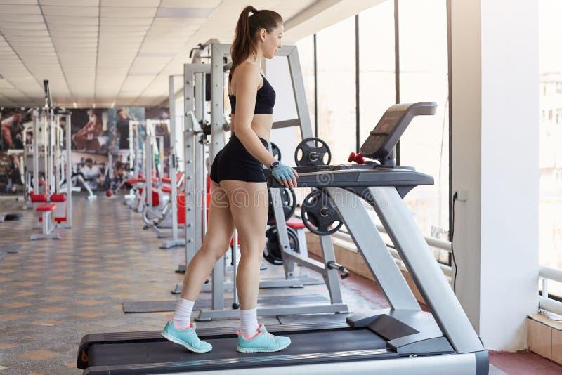 Het beeld van aantrekkelijke jonge vrouw in zwarte eenvormige sporten, warmt op, klaar voor het lopen op tredmolen, bezoekenfitne stock fotografie