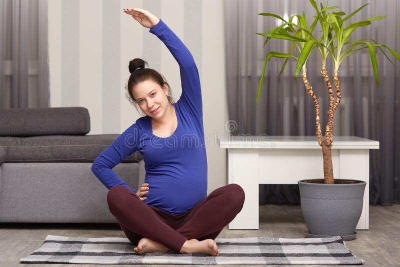 Het beeld van het charmeren van vrouw verwacht kind, doet sport thuis, behandelt gezond haar, draagt blauwe sweater en de beenkap royalty-vrije stock foto