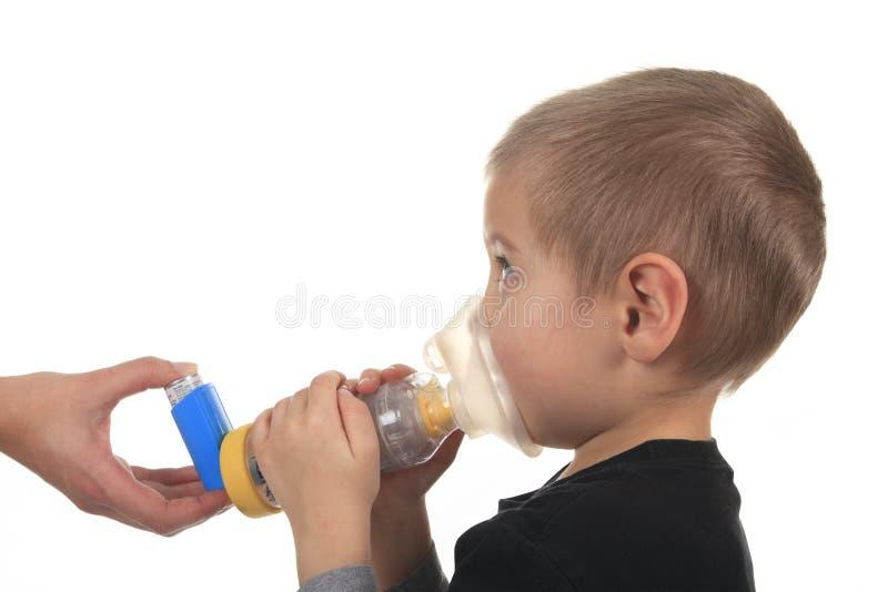 Het beeld van de close-up weinig jongen die inhaleertoestel voor astma met behulp van stock foto