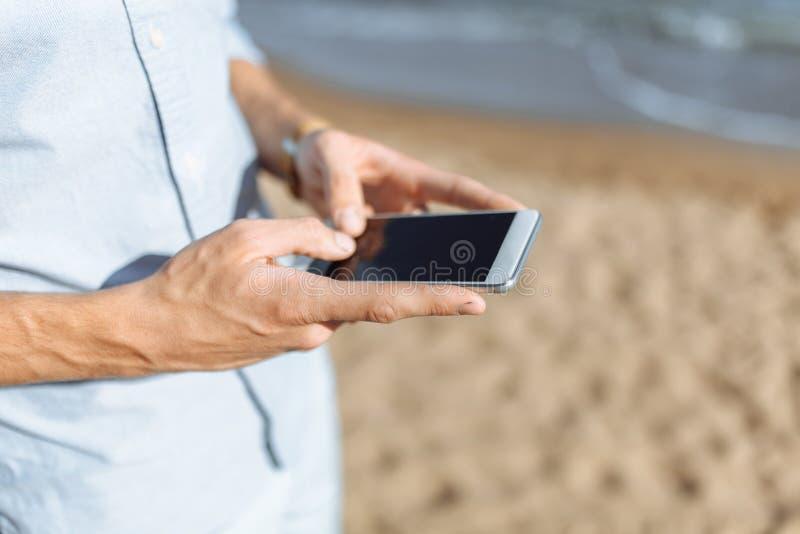 Het beeld van de handen met de telefoon, op de achtergrond van het strand, mededeling, geschikt om te adverteren, teksttoevoeging stock foto's