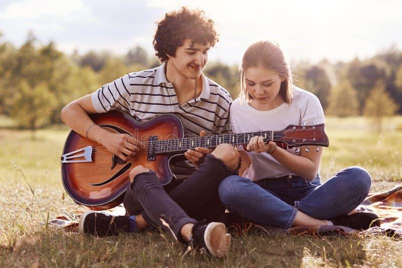 Het beeld van de jonge knappe mens met donker krullend haar onderwijst het spelen gitaar haar vriend, heeft het paar picknick in  stock fotografie