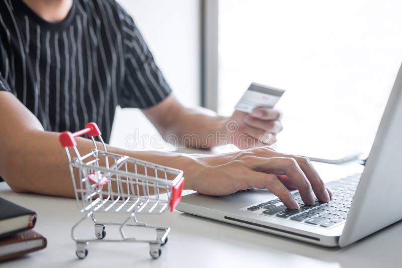 Het beeld van de Jonge mens die smartphone voor online het winkelen website gebruiken en betaalt door creditcard, Online betaling stock afbeeldingen